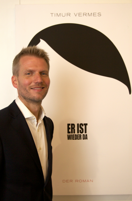 Felix Rudloff, publisher of Eichborn, poses with the cover of Er ist wieder da by Timur Vermes