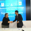 Carolyn Reidy, CEO of Simon & Schuster, signs a distribution agreement with Mr. Li Rui Hwa, VP of Yilin Press at the Frankfurt Book Fair