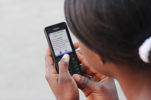 A Ghanaian woman reads South African independent publisher Modjaji's Love Interrupted on her mobile phone.