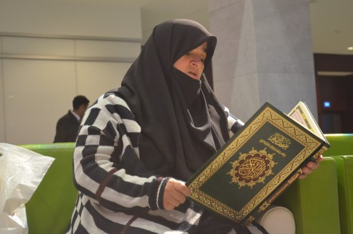 A visitor quietly recites some holy verses.