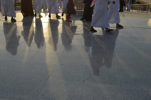 Traditional dress casts long shadows as evening approaches.