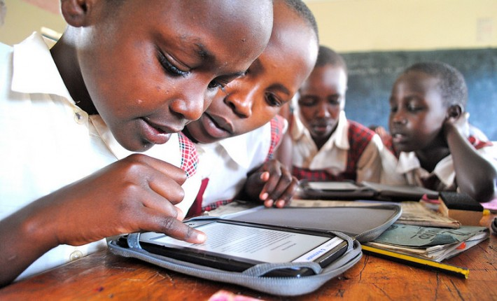 Students reading a digital book on an e-reader, both donated by Worldreader (Image courtesy of Worldreader)